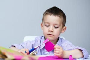 Junge schneidet Papier mit einer Schere foto