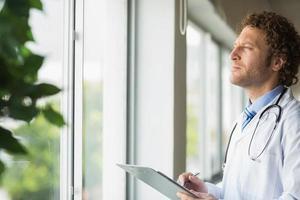 nachdenklicher Arzt mit Zwischenablage foto