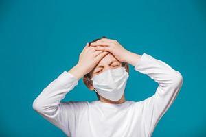 Junge trägt Schutzmaske mit Kopfschmerzen foto