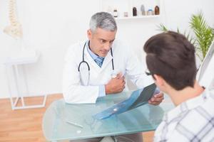 Arzt, der mit seinem Patienten Röntgenstrahlen betrachtet