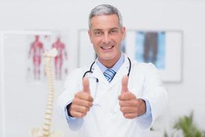 glücklicher Arzt, der Kamera mit Daumen hoch betrachtet foto