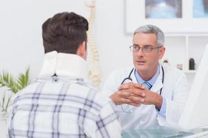 Arzt spricht mit dem Patienten, der eine Halskrause trägt foto