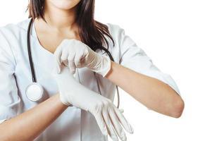 Arzt zieht weißen sterilisierten medizinischen Handschuh an, um die Operation durchzuführen foto