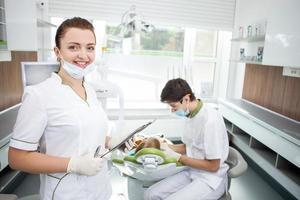 Ein professioneller männlicher Zahnarzt arbeitet mit dem Patienten foto
