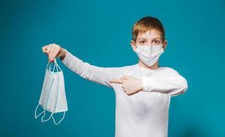 Junge, der Schutzmaske trägt, die auf Masken zeigt foto