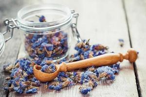 gesunder Vergissmeinnicht-Tee in Glas und Holzlöffel. foto
