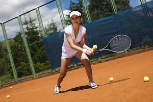 junge Tennisspielerin auf dem Platz foto