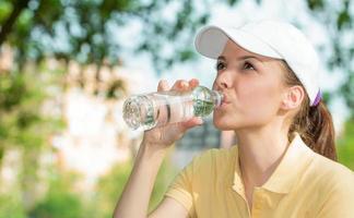 durstige Frau, die frisches Wasser trinkt, draußen. Sportmädchen mit Mütze foto