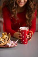 Frau mit Tasse heißer Schokolade und Weihnachtsbonbons. Nahansicht foto
