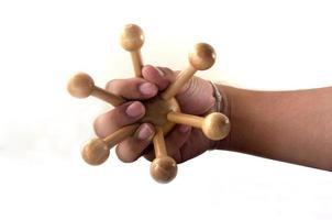 Holzobjekt für die Körpermassage in der Hand foto