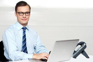 hübscher korporativer Mann, der auf Laptop bindet foto