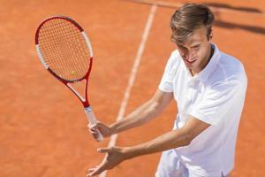 junger Mann, der Tennis spielt foto