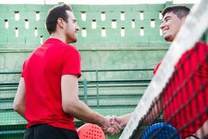 Freunde Händeschütteln im Paddle-Tennisfeld foto
