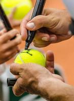 Tennisspieler gibt nach dem Sieg ein Autogramm foto