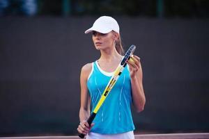 Frau spielt Tennis in Mütze foto