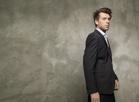 erwachsener Geschäftsmann, der den schwarzen Anzug trägt foto