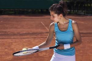 junges Mädchen, das Tennis am schönen Wetter spielt foto