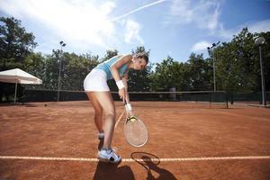 schönes junges Mädchen, das Tennis spielt