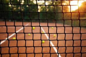 Tennisnetz Nahaufnahme mit Bällen im Hintergrund foto