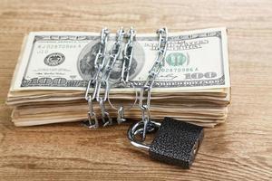 Dollarwährung mit Schloss und Kette auf Holztisch foto