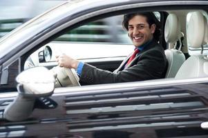 Firmenmann, der sein Auto fährt foto