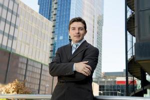 attraktiver Geschäftsmann des Firmenporträts, der im Freien städtische Bürogebäude steht