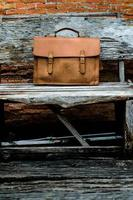 braune Leder-Laptoptasche Corporate auf altem Holzstuhl foto