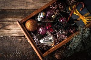 Holzkiste mit Weihnachtsschmuck und Geschenk Draufsicht foto