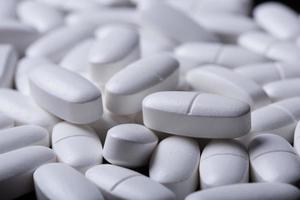 weiße Pillen auf dem Schwarz foto