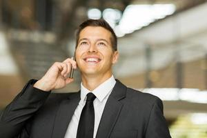 männlicher Firmenarbeiter, der auf Handy spricht foto