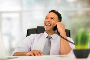 Firmenangestellter mittleren Alters, der am Festnetztelefon spricht foto