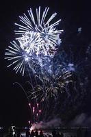 Brillantes Feuerwerk, das am Himmel über Wasser explodiert foto
