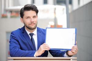 angenehmer Mann, der mit Papieren am Tisch sitzt foto