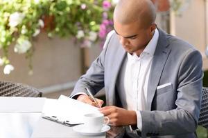 hübscher Geschäftsmann, der Notizen macht foto