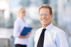 angenehmer Geschäftsmann, der nahe Büro steht foto