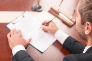 angenehmer Anwalt, der Papiere unterschreibt foto