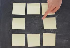 Frauenhand, die leere Klebenotizen auf Tafel schreibt foto