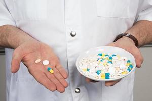 Pillen, Tabletten und Drogen häufen sich in der Hand des Arztes, foto