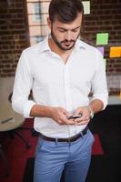 Gelegenheitsgeschäftsmann, der am Telefon eine SMS sendet foto