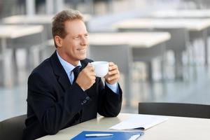 schöner Geschäftsmann, der am Tisch sitzt foto