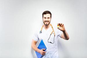 hübscher Arzt zeigt Pillen foto