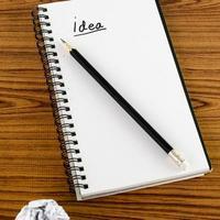 zerknittertes Papier und Bleistift mit Notizbuch foto