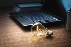 Glühbirne auf Holztisch mit Laptop foto