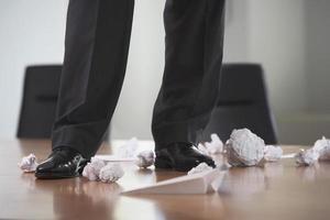 Beine auf Konferenztisch mit zerknitterten Papieren foto
