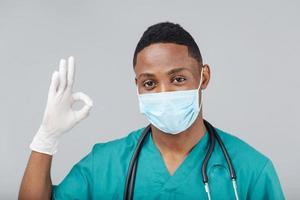 Afroamerikanerarzt mit ok Handzeichen nahe grauem Hintergrund