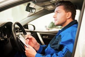 Mann untersucht Auto. foto