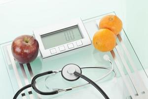 Apfel, Clementinen mit Sethoskop auf Schuppen foto