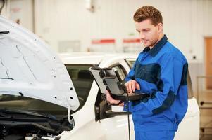 Mechaniker untersucht Auto. foto