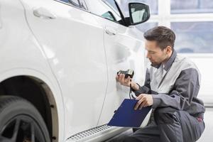 männlicher Reparaturarbeiter, der Autolack mit Ausrüstung untersucht foto