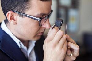 Juwelier untersucht Diamant durch Lupe foto